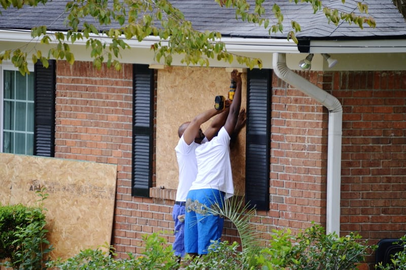 image of men putting plywood over windows