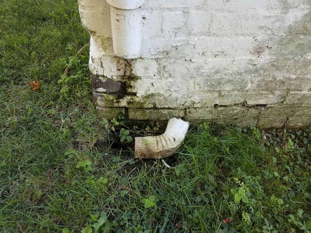 a broken downspout with water pooling around the base of a house