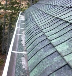 granules from shingles laying in gutter showing roof damage