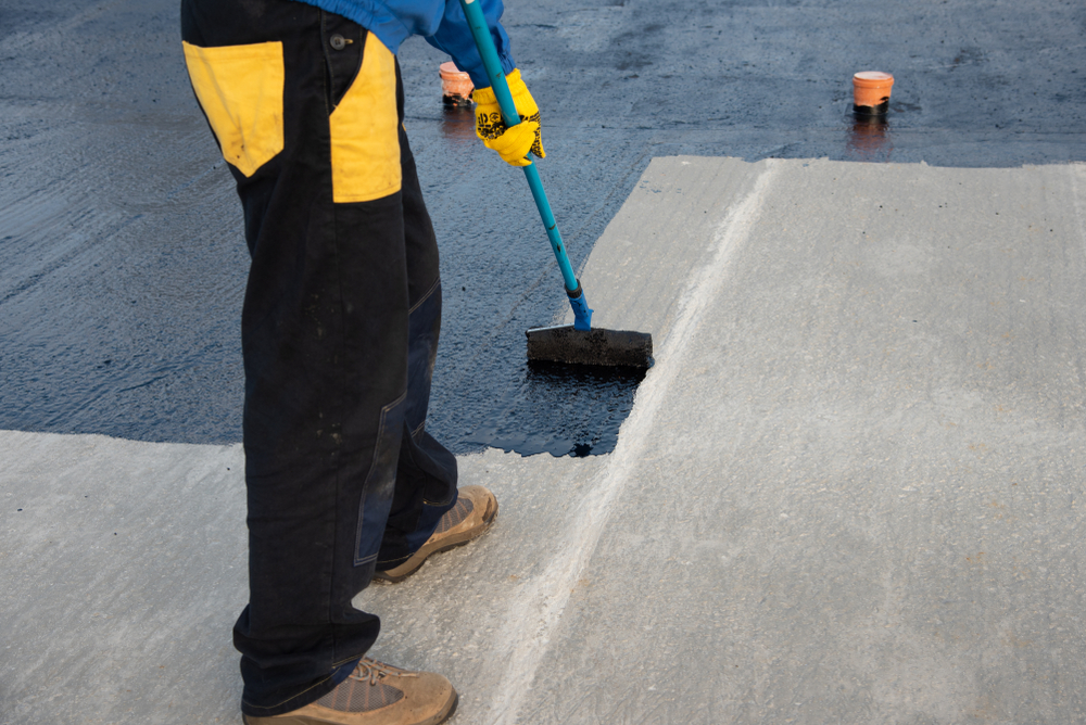 photo of roofing professional applying liquid modified bitumen roofing to the top of a flat roof