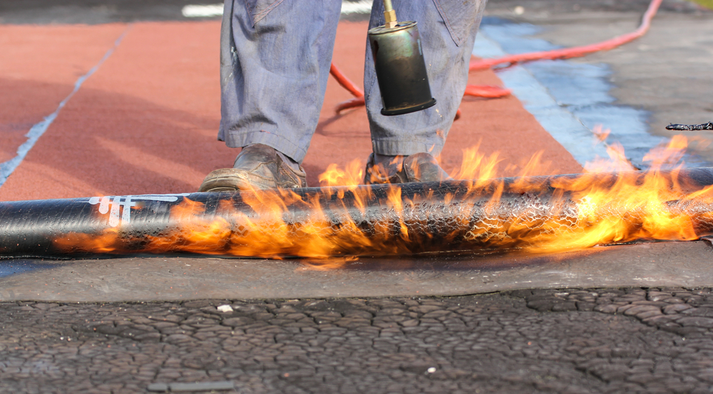 worker using heat and fire to apply roofing for a commercial flat roof